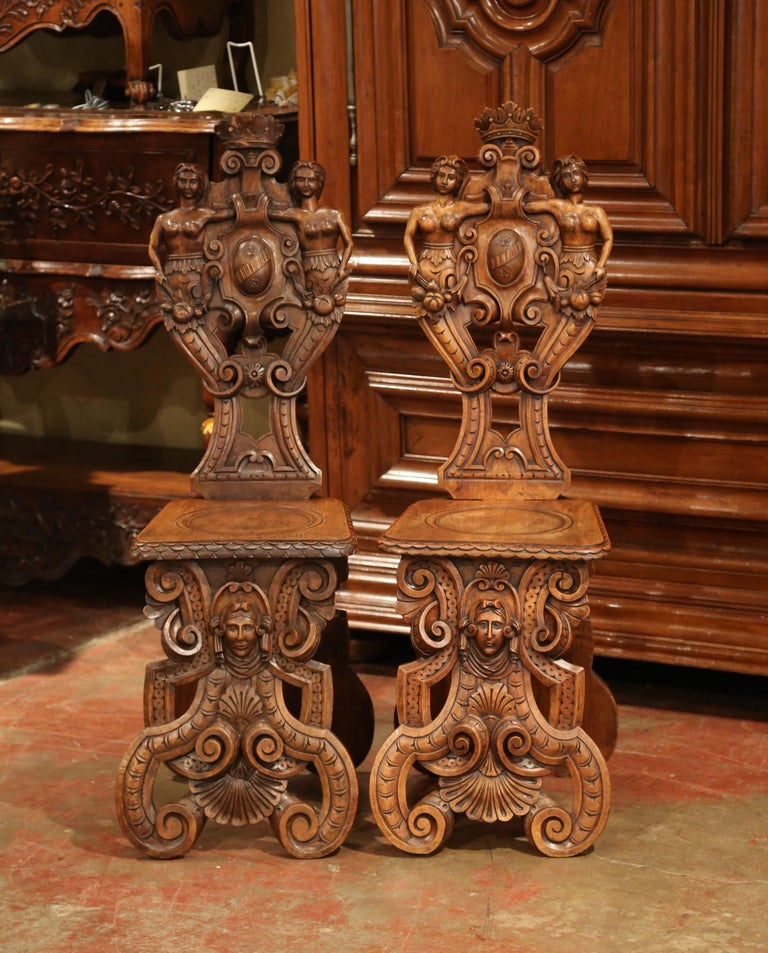 Decorate a hallway with this important pair of antique Sgabello chairs. Crafted in Italy circa 1860, each Renaissance stool has a back which first made an appearance in Renaissance Italy. The backs are heavily ornate with sculptural and symbolic