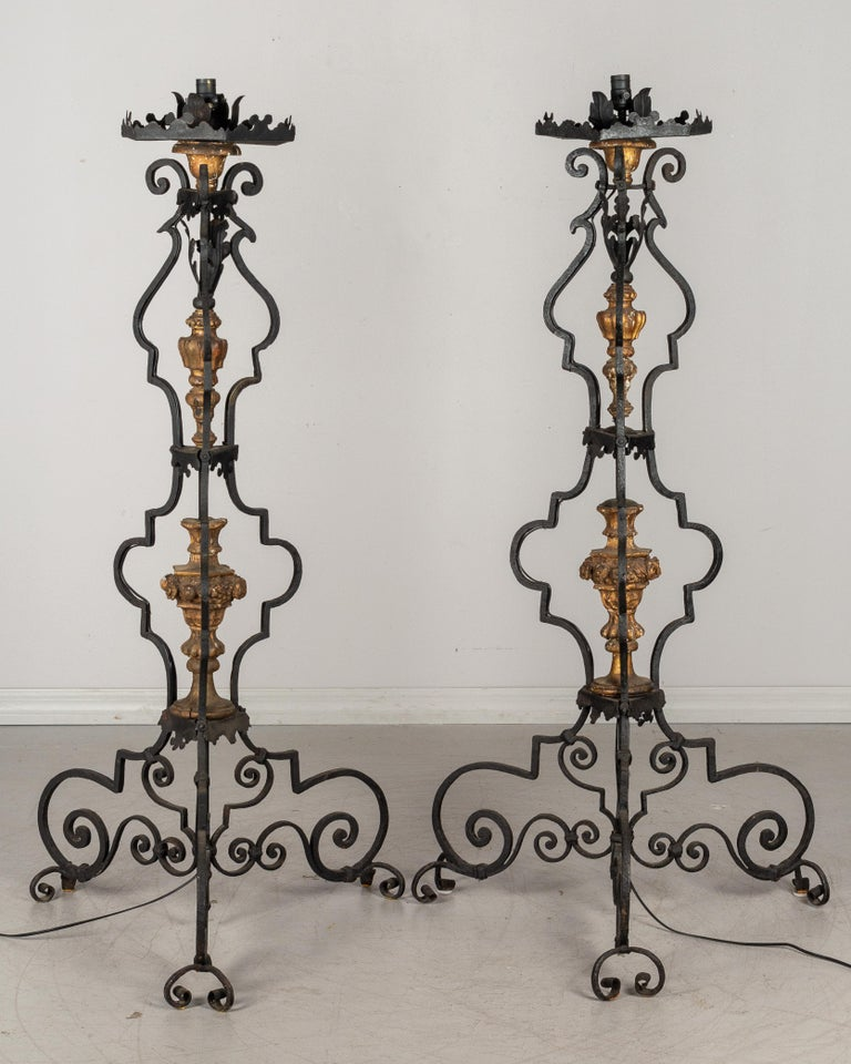 A pair of large 19th century Italian wrought iron floor torchieres with carved gilded wood decoration, circa 1800-1820. In good original condition with minor losses. Wired for use as floor lamps. Shown with black drum shade (not included). Please