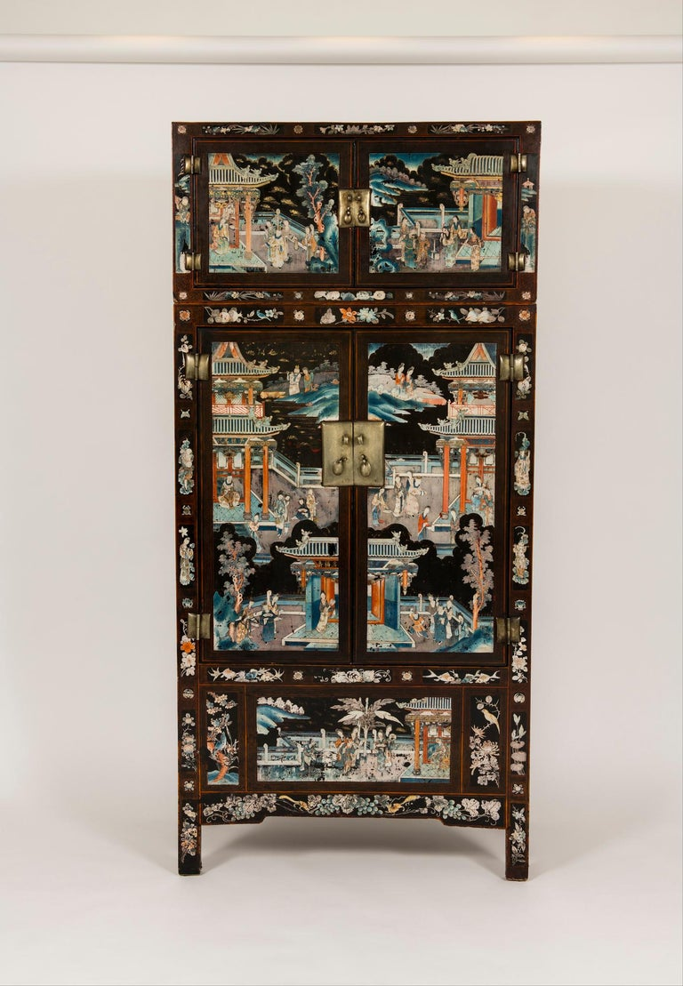 A spectacular pair of early 20th century Chinese lacquered Ming Style compound cabinets with painted scenes of figures in a temporal garden landscape. Still vividly colored, the lavish decorations cover the cabinets from top to bottom, complemented