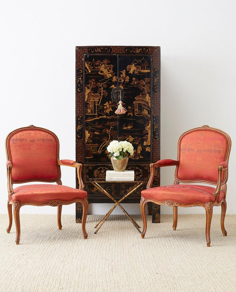 Fabulous pair of French carved walnut fauteuils made in the Louis XV style featuring a Chinese silk style upholstery with an antique look. Newly upholstered with a rich fabric that displays orange and red hues. The frame features a shaped back with
