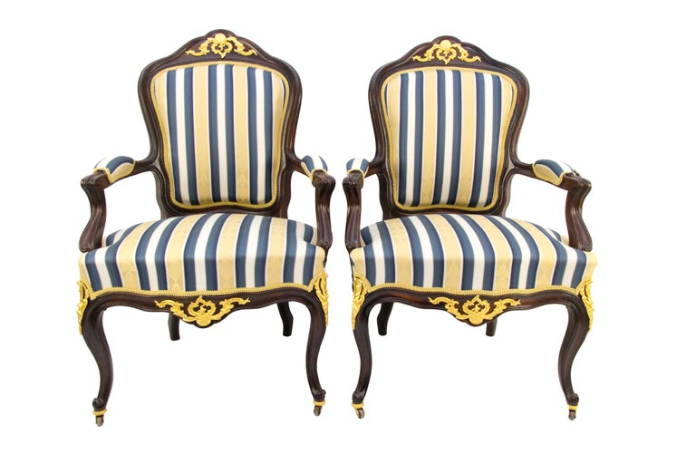 Pair of Louis XV style armchairs / Fauteuils from the late 19th century is made of walnut wood, with an upholstered seat, armrests and a backrest, decorated with gilt bronze mounts. The front legs of the armchairs are cabriole, on rollers. These