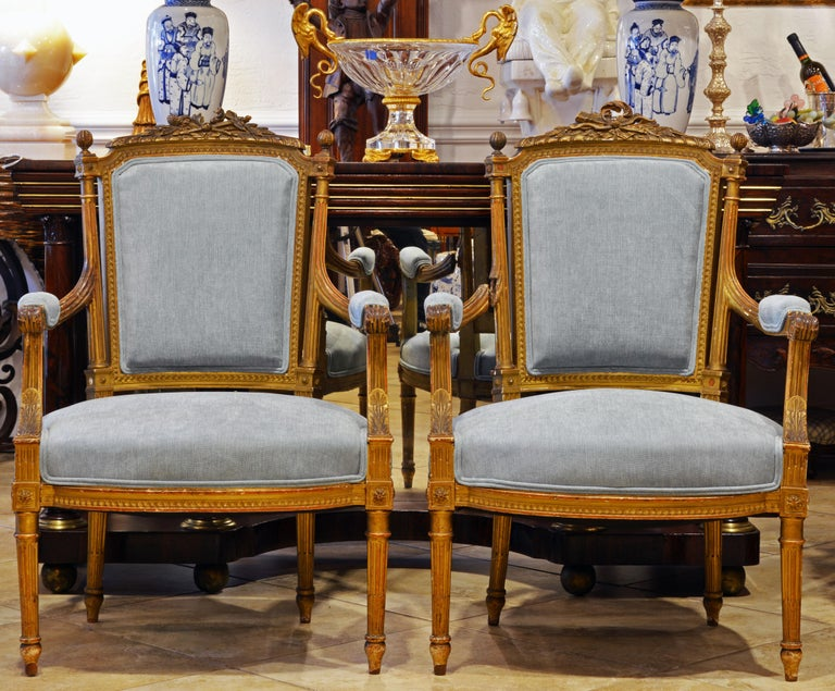 These elegant Louis XVI style open armchairs features a classical carved crested back, a beautifully carved frame, recent upholstering covered with subdued blue fabric and circular reeded tapering legs typical of the Louis XVI style. The gilt is