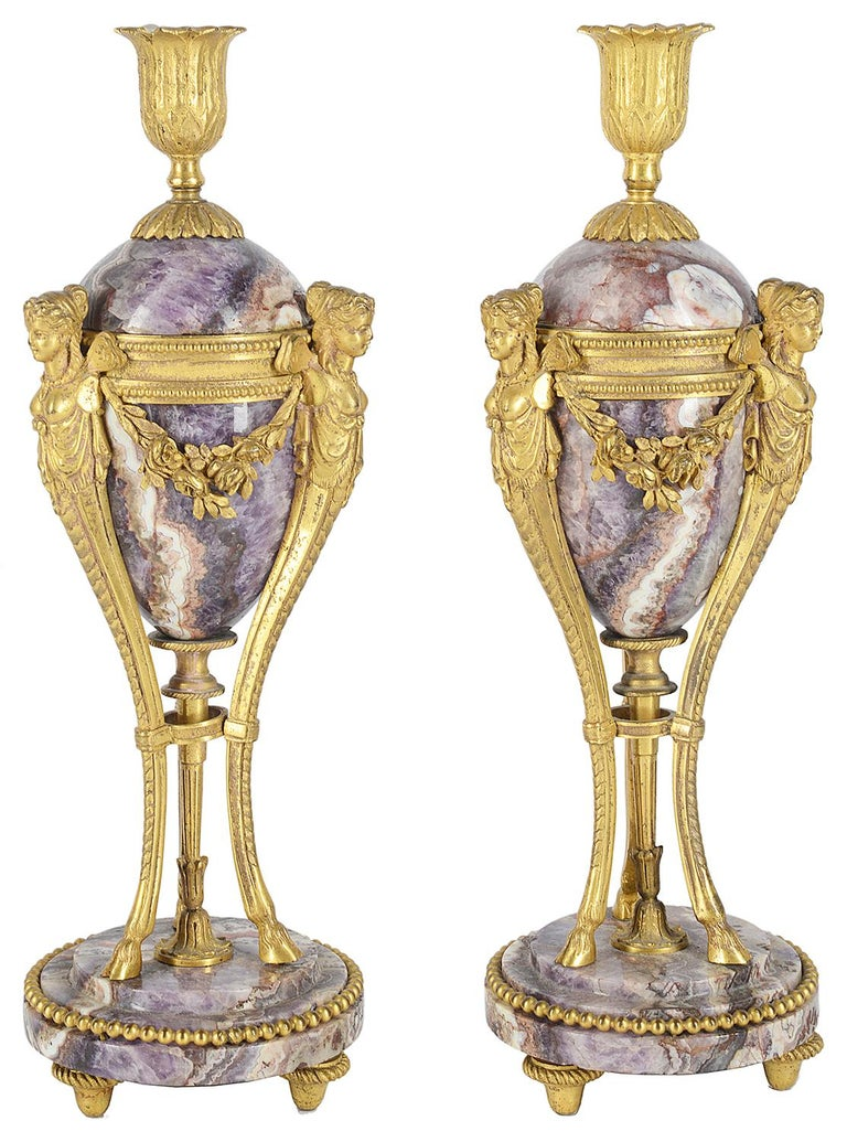 A very good quality pair of early 19th century marble and gilded ormolu candle sticks, each with winged female monopodia mounts, foliate swag decoration, tripod supports terminating in hoof feet and marble bases.