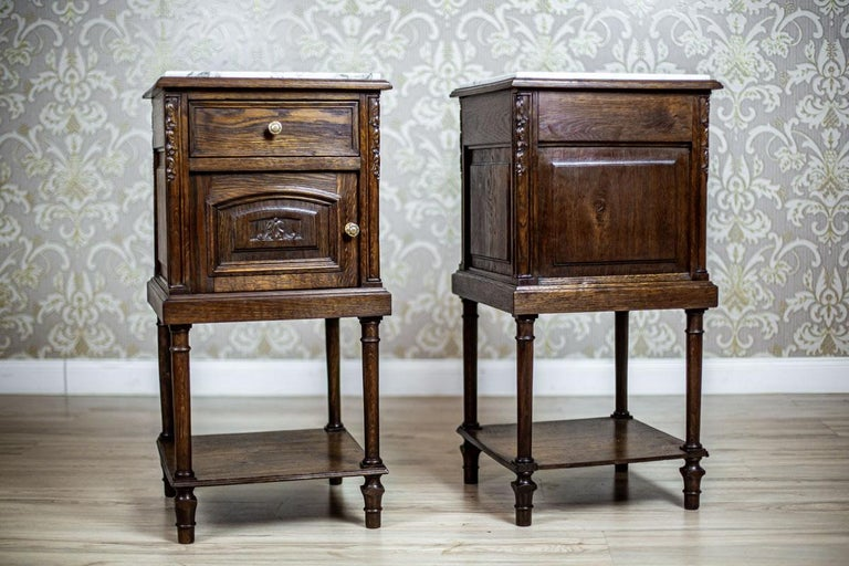 We present you two oak nightstands with a white marble top.