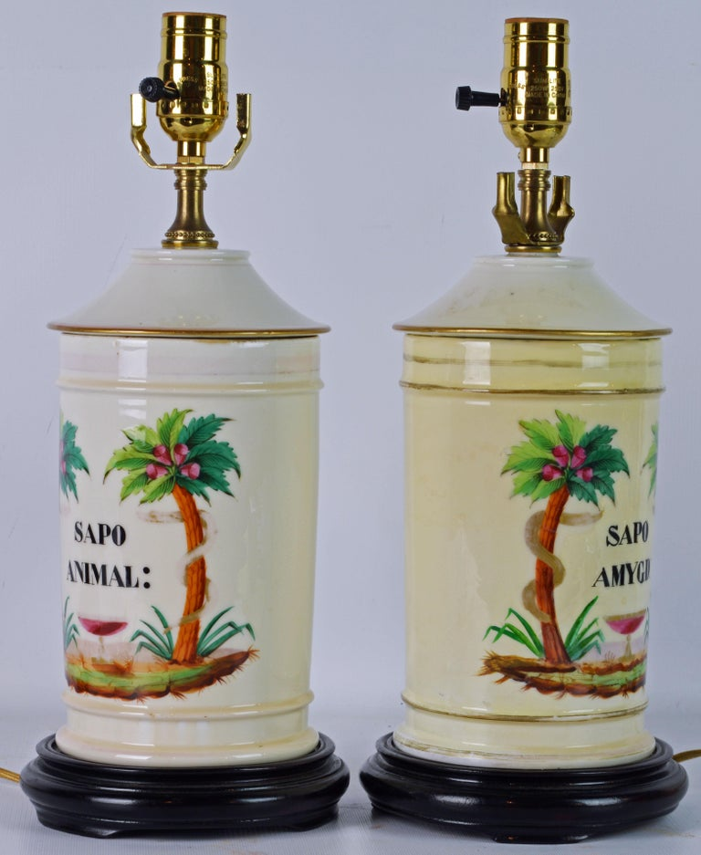 These French Apothecary Jars are by 'Gosse a Paris' but because they are mounted as table lamps with wood bases, the mark is hidden. The motif is very tropical with a pair of coconut palms, stems wrapped by serpents, flanking a centerpiece bowl