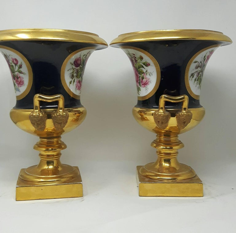 A heavily gilded pair of French Campana vases in the Napoleonic style, ornately painted with cartouches of flower bouquets. The base of the handles is decorated with a moulded head of Pan. French, Paris porcelain, circa 1890.