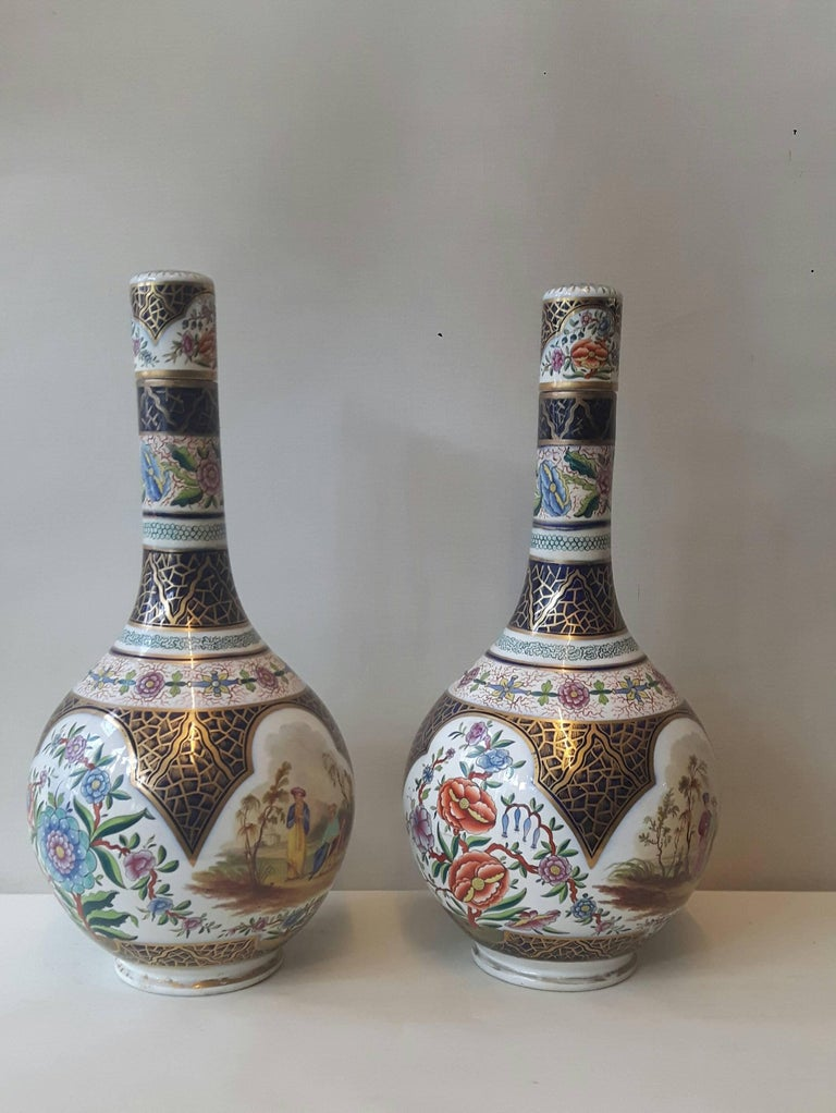 A lovely pair of bulbous-shaped Continental porcelain vases and covers. the central parts hand-decorated with cartouches of Eastern-style courting and flower scenes, the necks sporting bands of flower garlands, all on a heavily painted blue and