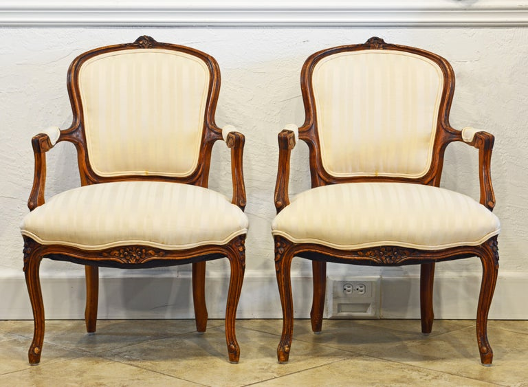 This pair of French Louis XV style carved armchairs are especially charming due to their relatively small size. They feature well carved walnut frames supporting upholstered backs, seats and armrests.