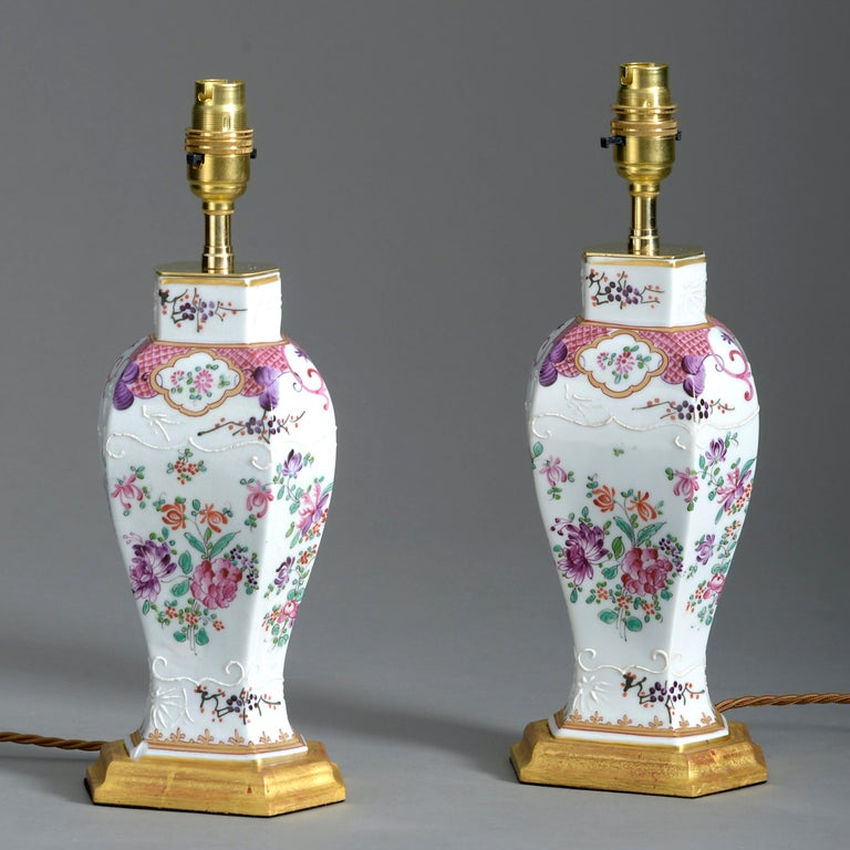 A fine pair of late 19th century famille rose porcelain vases by Samson in the Qianlong taste, of hexagonal baluster form and decorated throughout with floral vignettes. Now mounted upon water gilded bases and wired as table lamps.  Dimensions