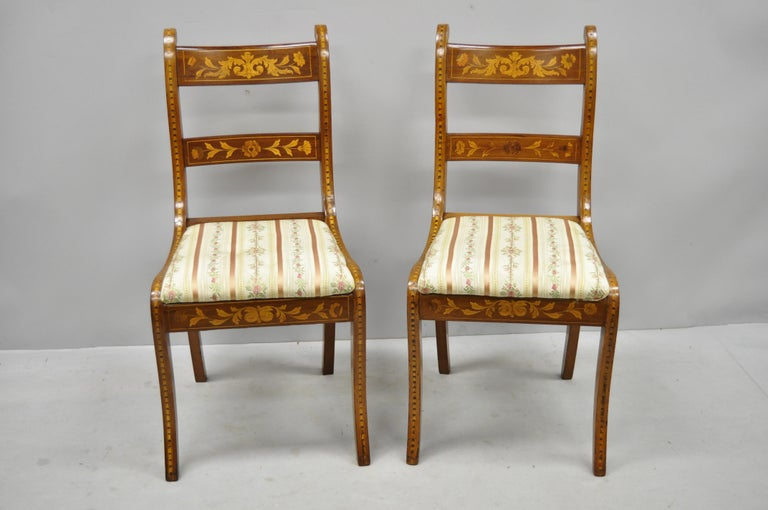 Pair of 19th century satinwood Dutch marquetry inlay Regency side chairs. Item features remarkable satinwood floral inlay throughout, solid wood construction, upholstered seat, shapely saber legs, very nice antique item, circa late 19th century.