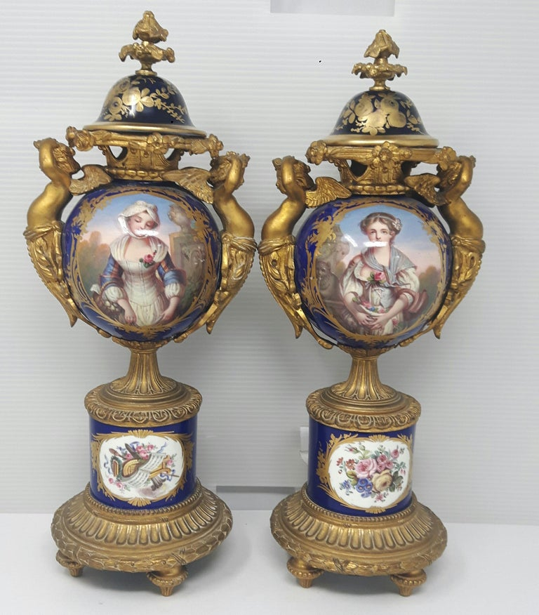 A pair of Sèvres-style vases painted with cartouches after Jean-Baptiste Greuze representing chastity and womanhood. The body of the vases is encased by an extremely high quality of gilt bronze cupidons or winged cupids and Rococo bases all in the