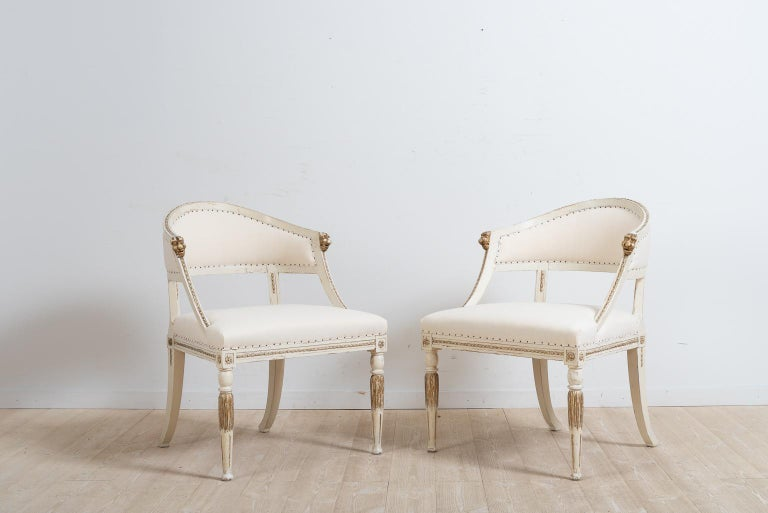 A pair of barrel back armchairs from northern Sweden. The chairs were manufactured in Gustavian style, circa 1880. Carved wooden decorations such as the gold painted lion heads at the end of each armrest. The chairs have their original paint which