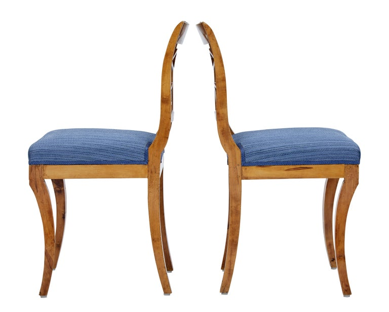 Elegant pair of birch side chairs circa 1890.  Shaped back with typical Scandinavian design in the back rest. Front sabre legs.  Upholstery in good clean condition.  Measures: Seat height 18