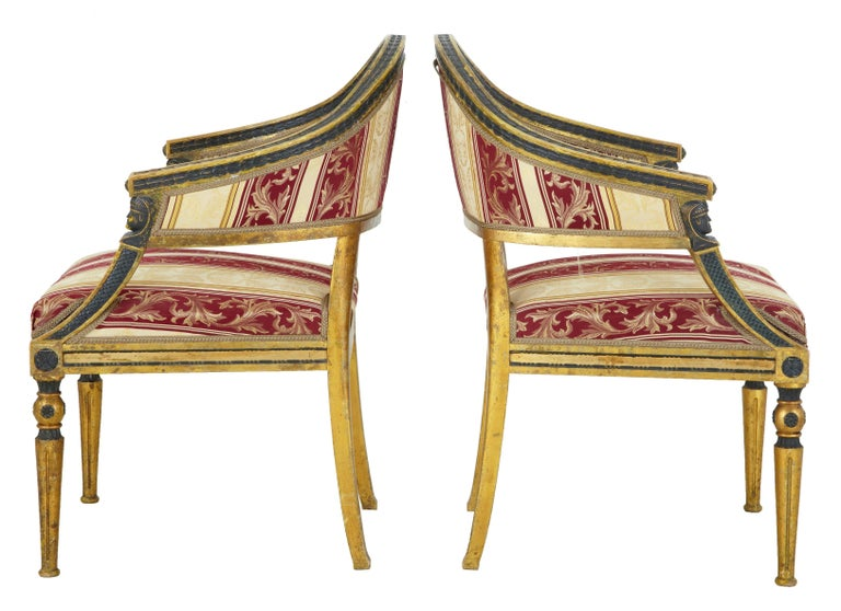 Pair of fine quality shaped back gilt armchairs, circa 1860. Unusual shaped back with ebonized leaf detailing contrasting with the gilt. Egyptian style mounts below the arms. Standing on tapered legs. Upholstered in later silk material.  Seat