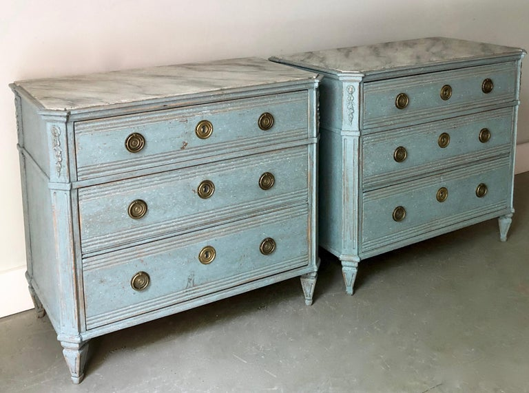 A pair of 19th century Swedish Gustavian style chests with marbleized wooden tops. Drawers with raised panels and bronze hardwares. Canted corner post with dentil molding under the shaped top on tapering reeded and fluted legs. Later light-blue