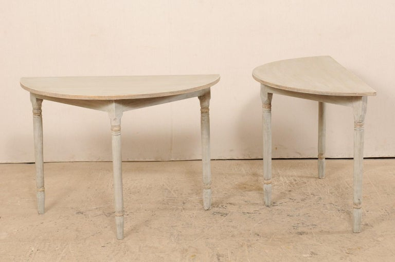 A pair of 19th century Swedish painted wood demilune tables. This pair of antique demilune tables from Sweden each features half moon tops over triangular-shaped aprons, and are raised on three rounded legs with turned carvings accentuating their