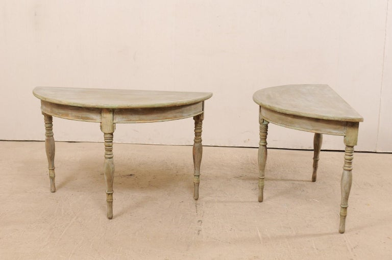 A pair of 19th century Swedish demilune tables. This pair of antique Swedish painted wood demilune tables features half moon tops over rounded aprons. The pair is raised on three beautifully turned legs. These demilune consoles tables have a