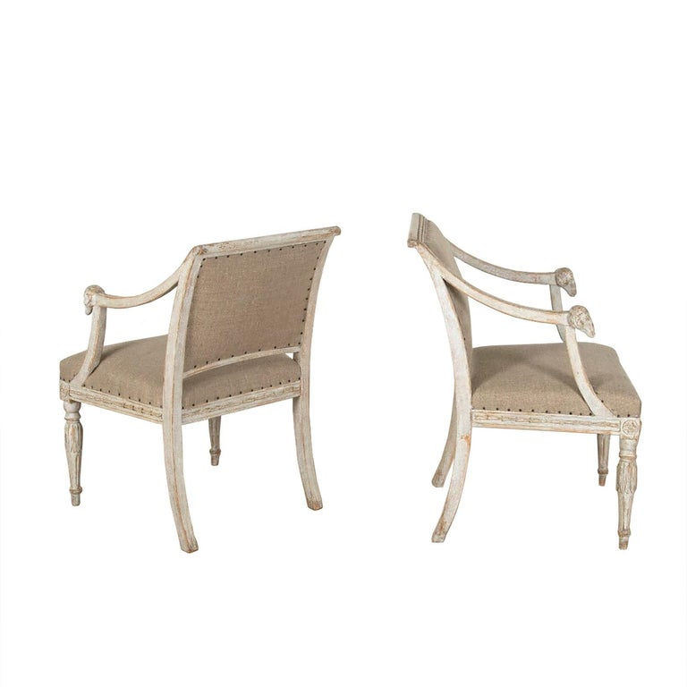 This exceptional pair of Swedish 19th century chairs feature carved decorative detailing with ram heads.