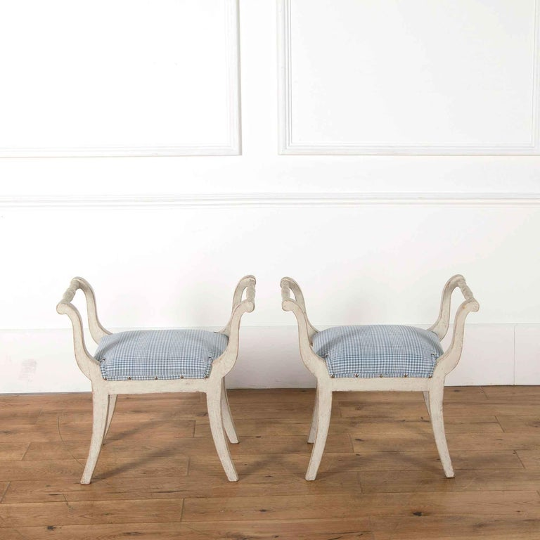 A pair of 19th century painted Gustavian style stools recovered in antique Alsace linen.