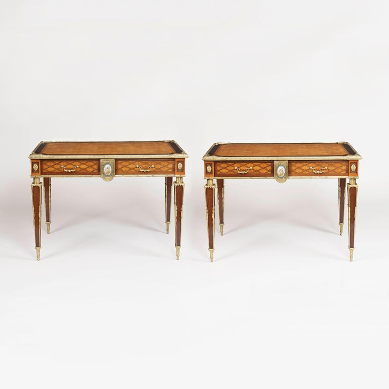A rare pair of tables attributed to Donald Ross of London  Constructed in citronnier, ebony and harewood, and dressed with a porcelain plaque in the 'Sevres' manner, and adorned with very fine bronze mounts. Throughout, the 'trellis and dot'