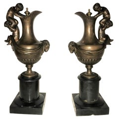 Pair of 19th Century Urns on Marble Stands Bearing Cherubs and Rams Heads