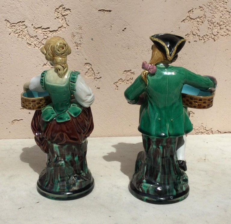 A charming pair of Victorian Majolica couple dressed holding a basket.