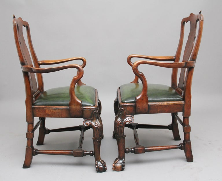 A superb pair of 19th century walnut armchairs in the early Georgian style, the shaped splat back with lovely sweeping shepherds crook arms, a recently upholstered green leather drop in seat and shaped seat rails, fabulous carved cabriole legs and