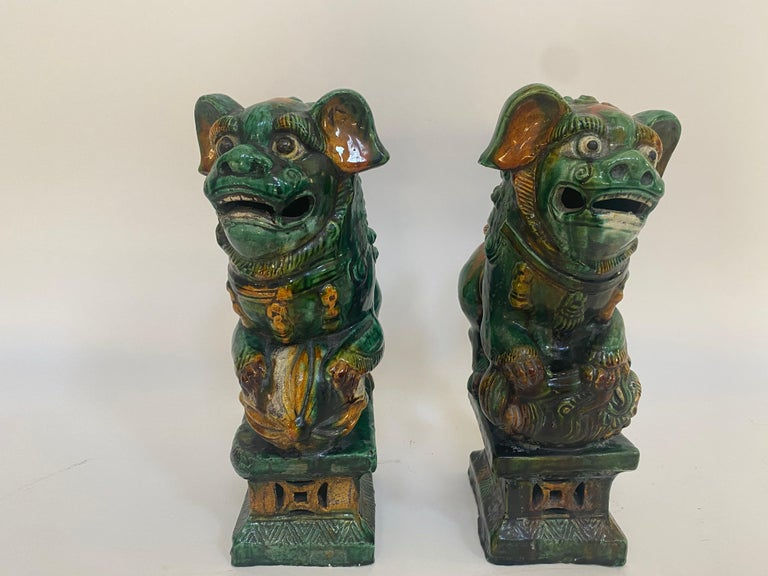 19th century Chinese tri-colored glazed foo lions. Beautiful pair of antique Chinese foo lions/dogs. The glaze still shines, there are minor chips here and there. Always standing in pairs, foo dogs are fantasy lions in Chinese mythology who serve