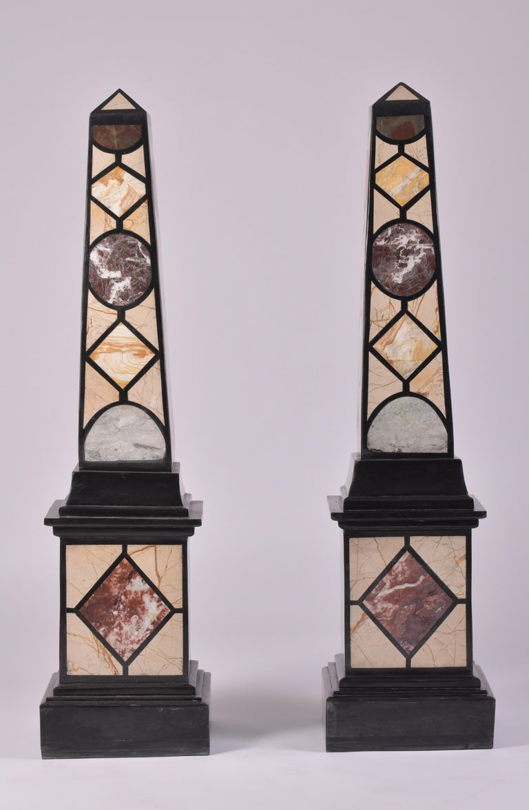 This sleek and very decorative pair of marble specimen obelisks set on a cubed base features a geometric designed pattern in green, purple, cream and brick red all outlined in black. Each obelisk measures 12 in – 30.5 cm square and 47 ½ in - 120.6