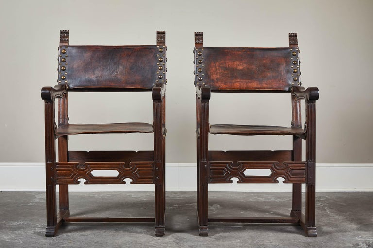 Peruvian hand carved reproduction of a French found antique. Dark stained wood frame, very sturdy and substantial. Leather sling seat and back with large nailhead detailing on leather seat and backrest. Set of eight available. Side chairs available