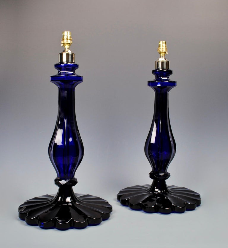 A superb pair of cobalt blue cut glass table lamps, each with moulded faceted baluster stems, and scalloped base.  Height: 19 in (48.5 cm) excluding electrical fitments and lampshades.  All of our lamps can be wired for use worldwide. A