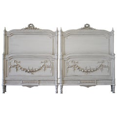 Pair of 20th Century Carved Painted Louis XVI Style French Beds with Rose Swags