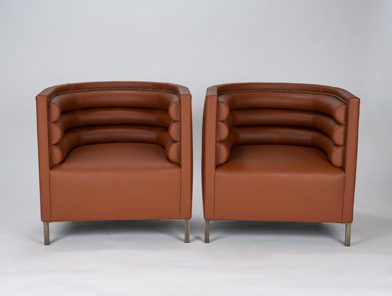 A pair of Italian channelled barrel back chairs professionally reupholstered in cognac leather with bronzed legs and nailhead detail.