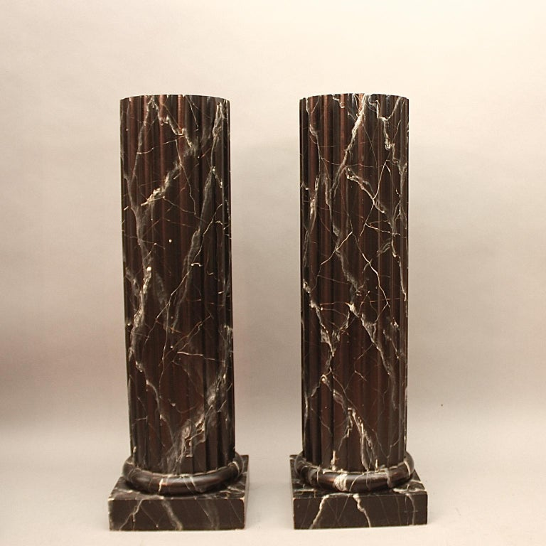 Pair of 20th century Italian painted black faux marble columns or pedestals, each with a fluted shaft and a base enriched with mouldings resting on a rectangular plinth. Made of wood and finely painted with delicate marble veins resembling Nero