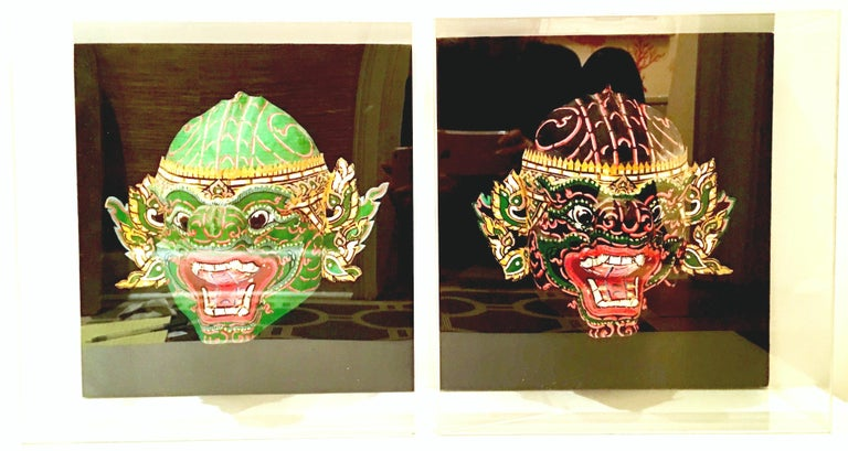 Pair of Javanese Paper Mâché hand-painted tribal celebration masks. Each mask is mounted on black linen in large Lucite shadow box frames. Each mask measures approximately, 11