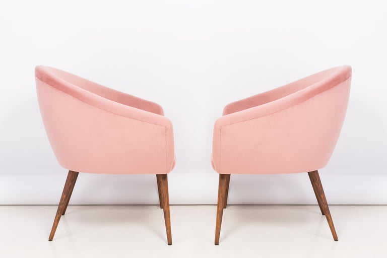 Very comfortable and stabile club seats. Produced in the 1960s in Poland. The whole armchairs are covered with high-quality velour color pink 2258. The armchairs are after a complete upholstery and wood renovation. We can prepare this set in another
