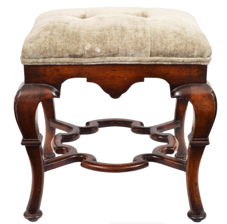 This pair of Spanish colonial style benches or ottomans feature a great sculptural form with robust cabriole legs joined by beautiful carved and shaped stretchers centering an inner partly circular space. The are upholstered and covered with a