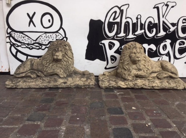 A pair of 20th century stone lions These wonderful well-weathered lions made from cast composite stone comprise a genuine (opposing) pair and are modeled after the famous Antonio Canova Lions that guard Pope Clement XIII's tomb. In very good