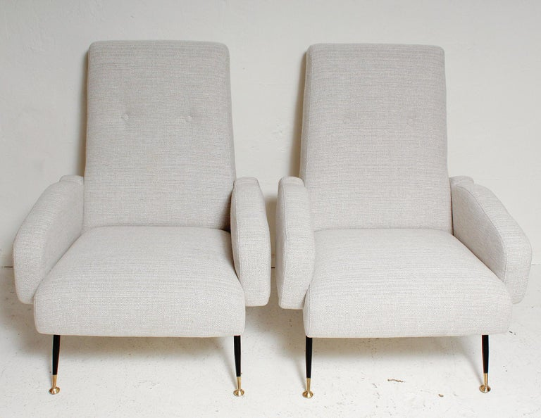 Oh-so-sexy pair of 1950s Italian lounge chairs, fully restored with all new foam, palest grey and cream upholstery, and freshly polished brass details.