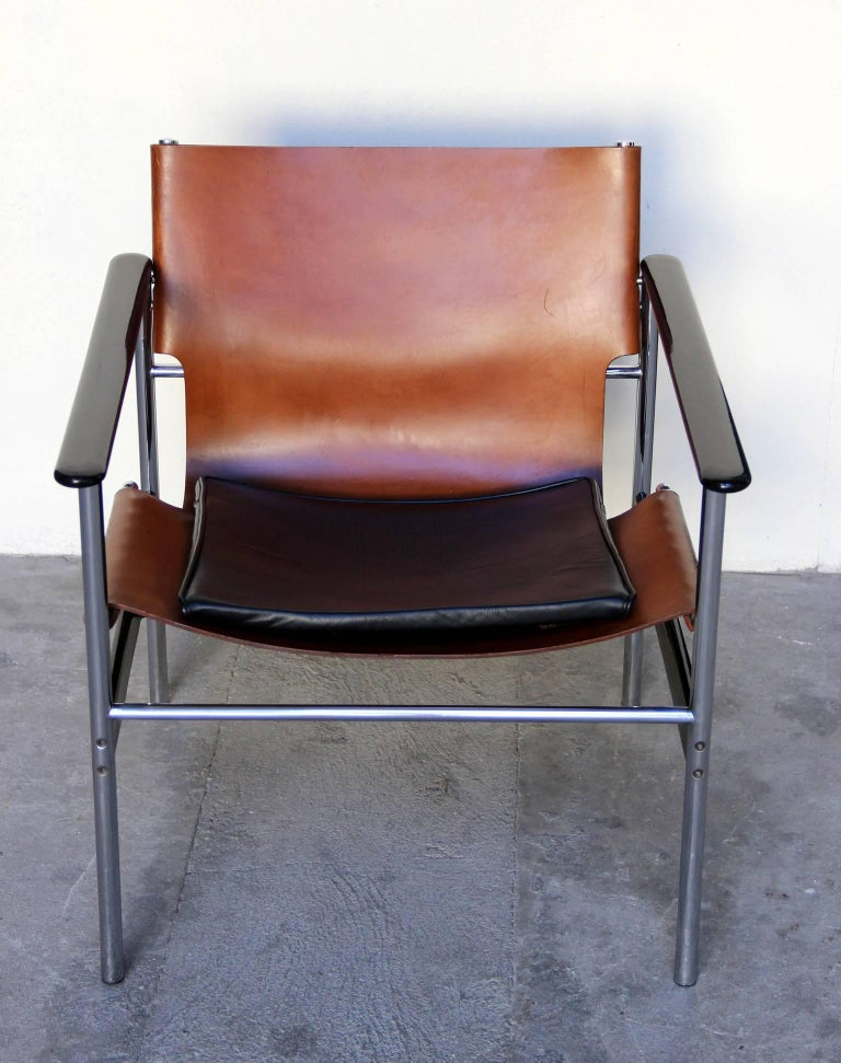 Pair of 657 sling lounge chairs with original tan leather sling seats with attached black leather seat cushion. In a tubular frame with black resin coated aluminum armrests. Made in 1964.