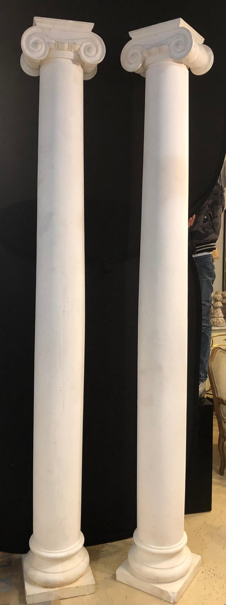 Pair of almost nine foot high columns having Corinthian carved capitals in an off white composite or fiberglass. Heavy and sturdy are these impressive and very large columns. They can go either inside or outside in the yard. Some minor chips or