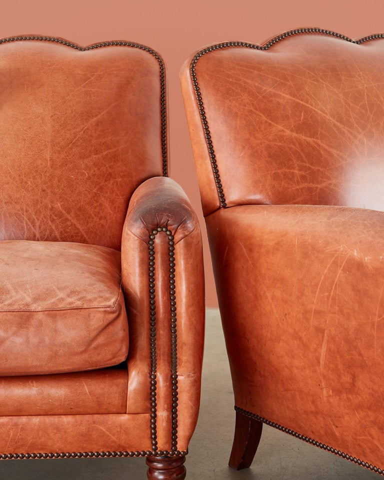 Fantastic pair of French art deco style terra-cotta leather lounge or club chairs hand-crafted by A. Rudin in Los Angeles, California. Generous hardwood frames covered in supple aged brick red or terra-cotta colored leather embellished with brass