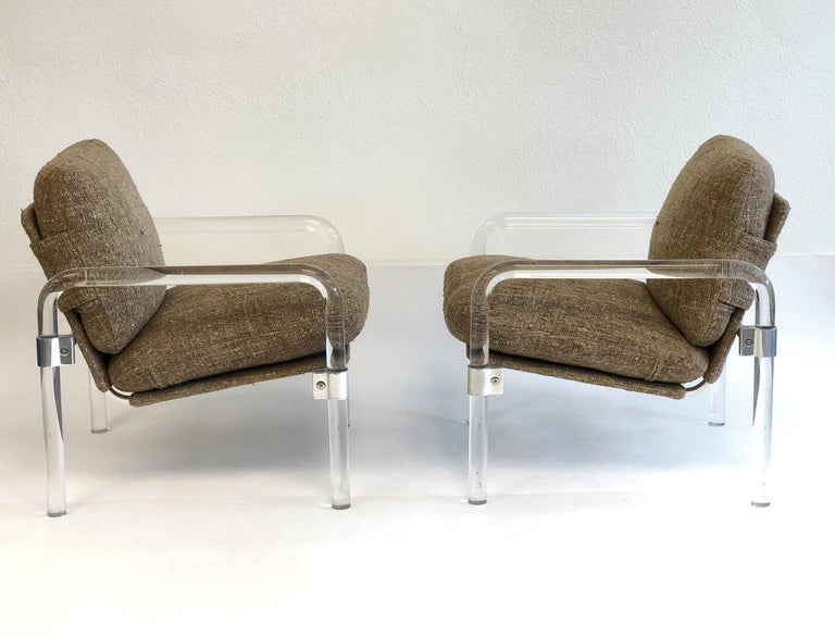 """A glamorous pair of clear acrylic and polish chrome """"Pipe Line Series 2"""" lounge chairs by Jeff Messerschmidt. Both chairs are signed, numbered(#162, #163) and dated 1982. The chairs retain original light brown fabric upholstered by a Palm Desert"""