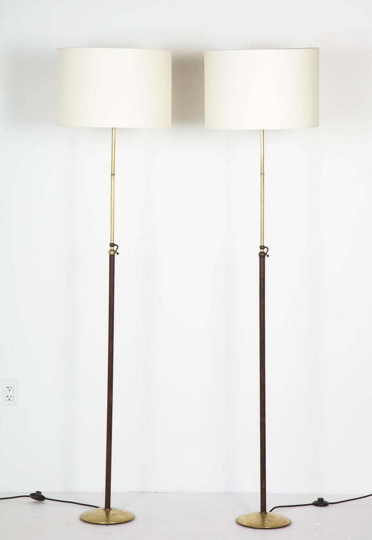 Pair of leather and brass adjustable floor lamps by Jacques Adnet, leather is original, brass has been lightly restored. Rewired. Base is 10'' in diameter, extends to 75''.