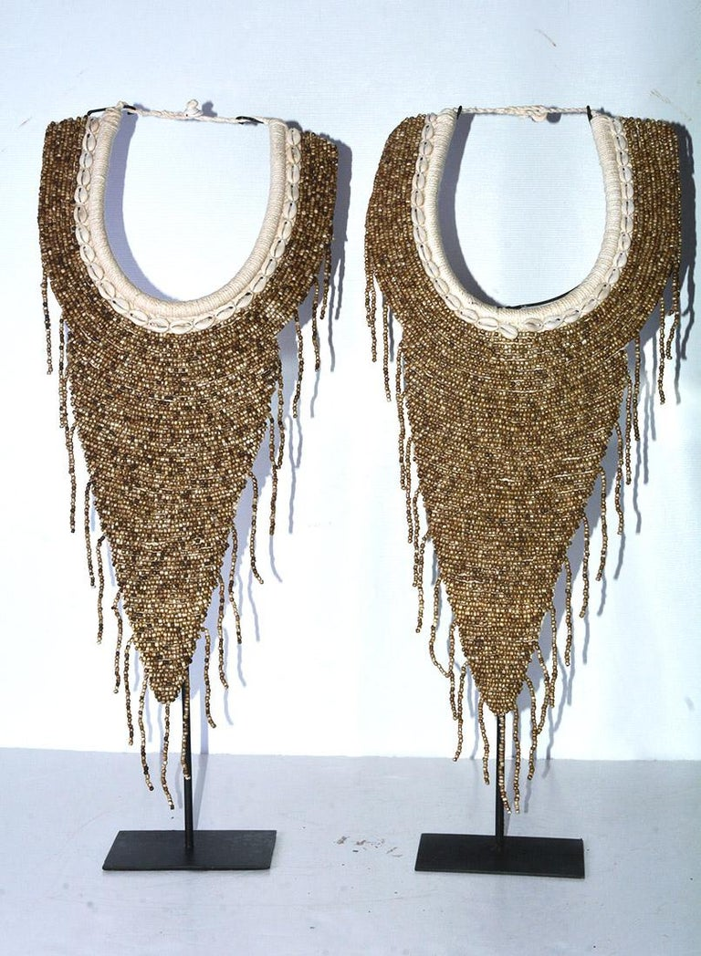 The highly decorative African bib necklaces are treated as works of art displayed on their black metal stands as sculptures. Near the necks are bent poles wrapped with twine. The next layer is a row of small sea shells. The bib is composed of curved