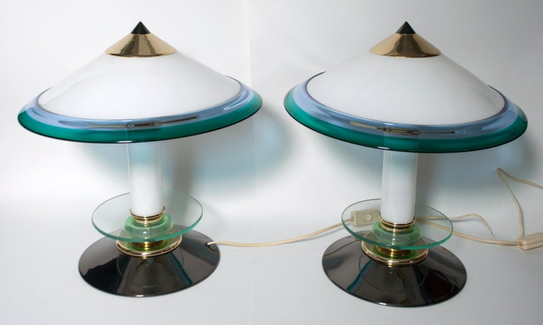 This pair of Murano glass lamps, produced in the 1980s, have a gunmetal metal base and brass parts. They were designed in the style of Ettore Sottsass, in the 1980s.