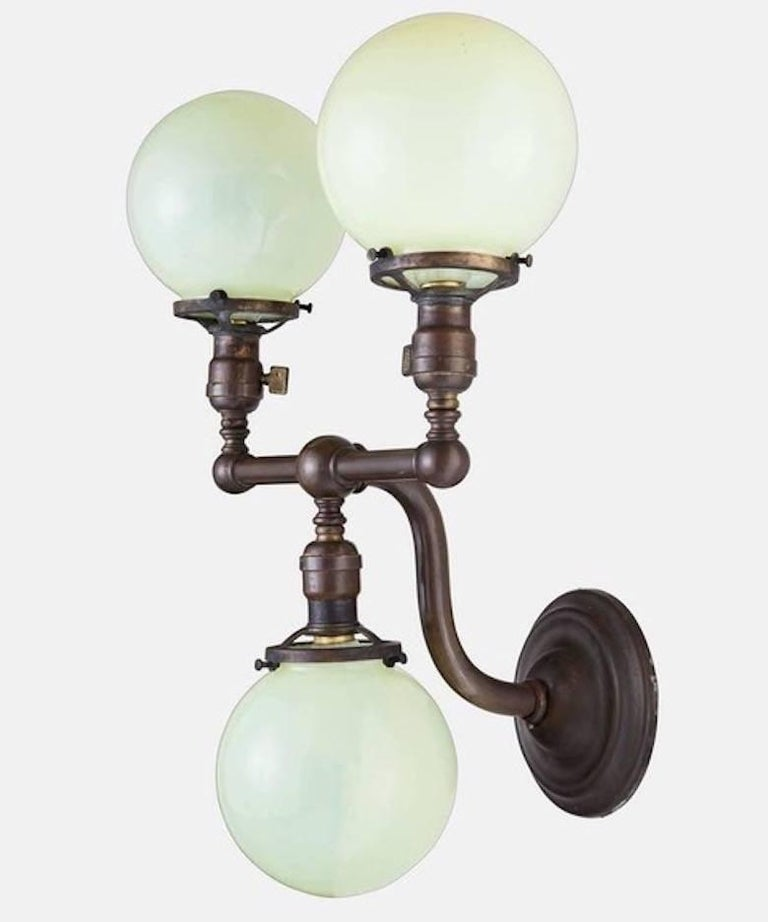 An elegant pair of brass scones with Vaseline glass globes, circa 1920s. Globes are six inches in diameter, hand blown, light green, slightly opaque. Brass fittings with three sockets. Brass has a rich patina.