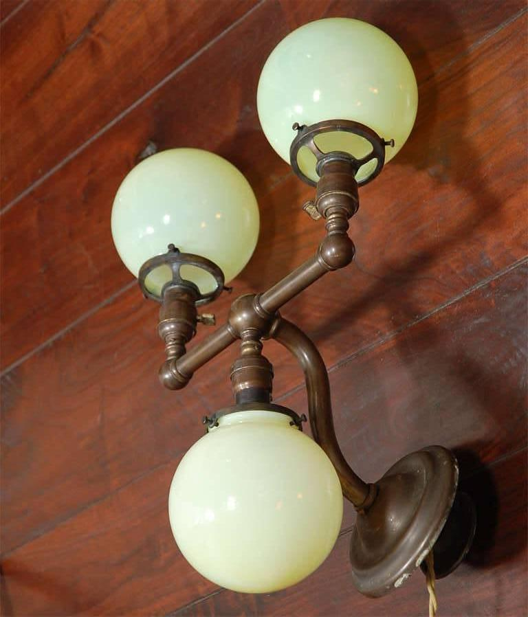 Pair of Aged Brass Sconces with Vaseline Glass Globes 'Triple' In Good Condition For Sale In Los Angeles, CA