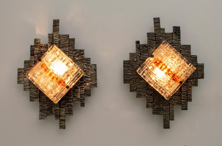 These wall lamps were created by the master glassmaker Albano Poli for his Poliarte company. The wall lamps have a patinated and handmade metal base, two squares in white relief glass with brick red serpentines. The sconces can be fixed vertically