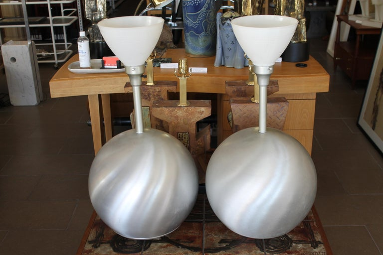 Pair of Raymor (Irving Richards) aluminum sphere lamps. We believe these were designed by Russel and Mary Wright and distributed/sold through Raymor. One of the lamps has a Raymor catchphrase label 'Modern in the Tradition of Good Taste'. Lamps have